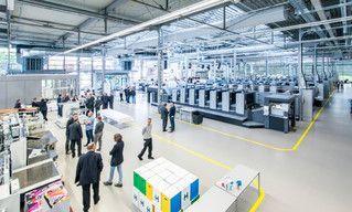 Halle mit mehreren Druckmaschinen von Heidelberg, Besucher und Mitarbeiter im Gespräch